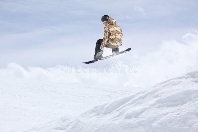 Летание Snowboarder на предпосылке снежного наклона Весьма спорт зимы, сноубординг стоковые изображения