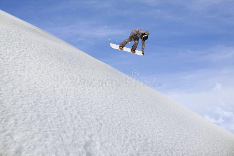 Летание Snowboarder на предпосылке снежного наклона Весьма спорт зимы, сноубординг стоковое изображение