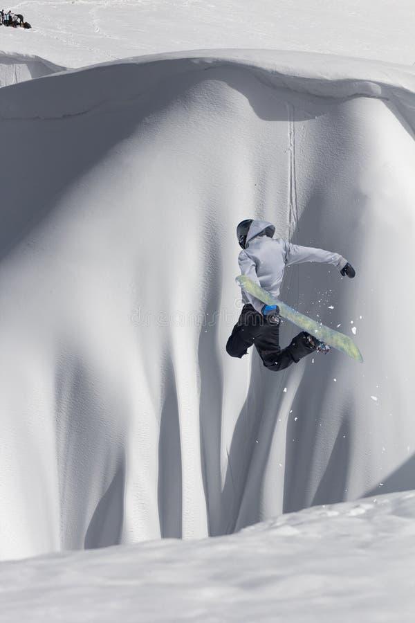 Летание Snowboarder на предпосылке снежного наклона Весьма спорт зимы, сноубординг стоковое изображение rf