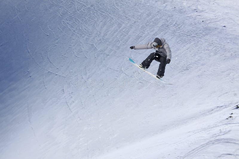 Летание Snowboarder на предпосылке снежного наклона Весьма спорт зимы, сноубординг стоковое фото rf