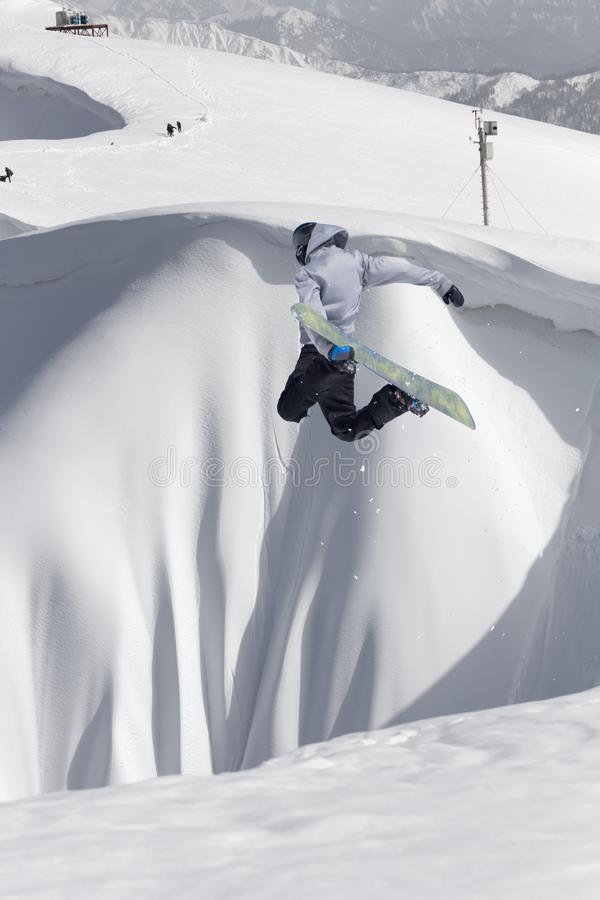 Летание Snowboarder на предпосылке снежного наклона Весьма спорт зимы, сноубординг стоковые фото