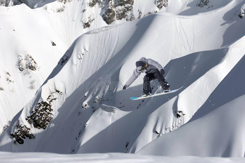 Летание Snowboarder на предпосылке снежного наклона Весьма спорт зимы, сноубординг стоковые изображения rf