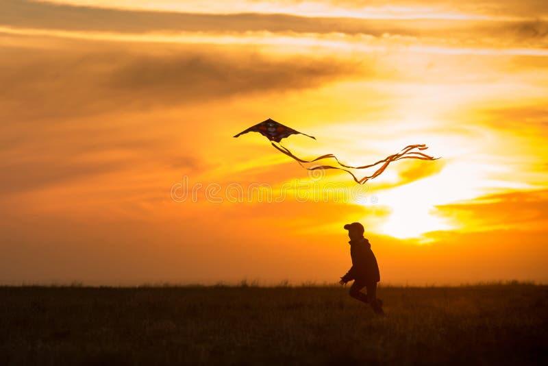 Летать змей Мальчик бежит через поле со змеем Силуэт ребенка против неба Яркий заход солнца стоковое изображение
