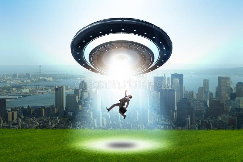 Летающая тарелка похищая молодого бизнесмена стоковое изображение