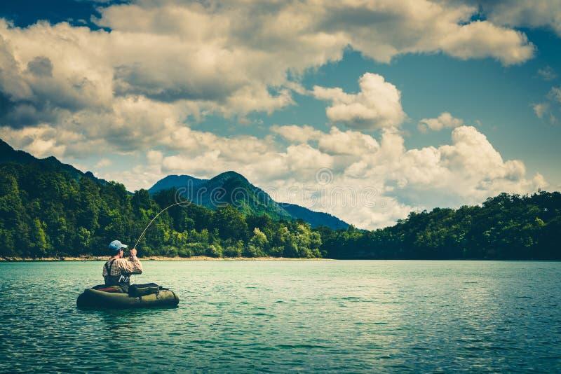 Летите рыболов на bellyboat воюя с большой форелью, Словенией стоковое изображение rf