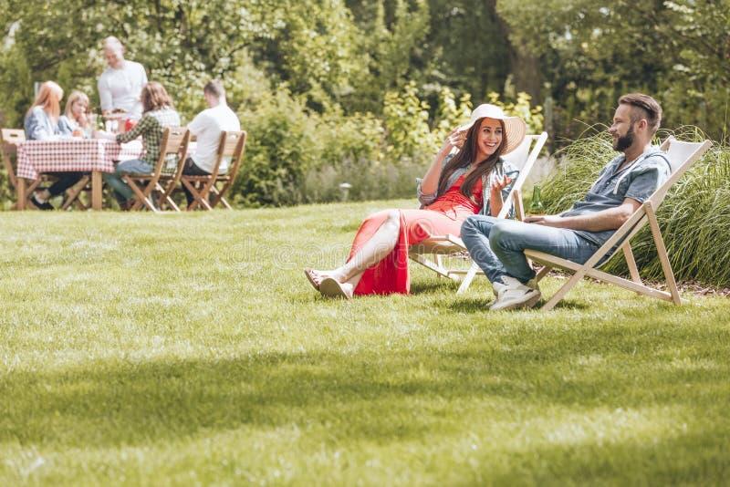 Летние каникулы в зеленых окрестностях Люди сидя на палубе ch стоковое изображение