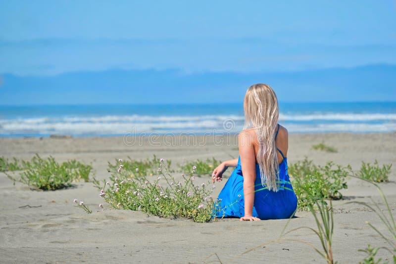 Летние каникулы на пляже Женщина на пляже смотря море стоковое фото
