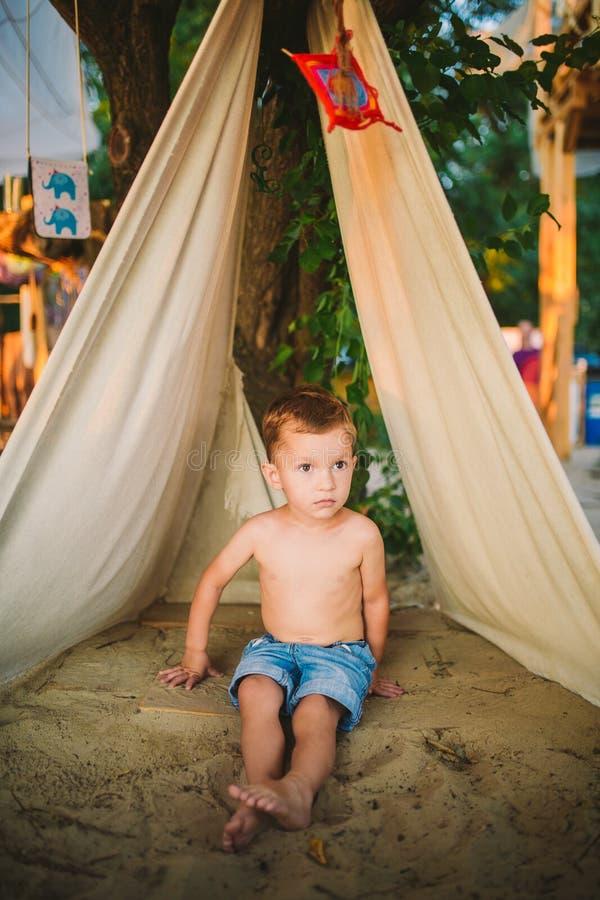 Летние каникулы темы, мальчик, кавказский ребенок играя в лесистом районе в парке на спортивной площадке во дворе ребенк в шатре  стоковые фотографии rf