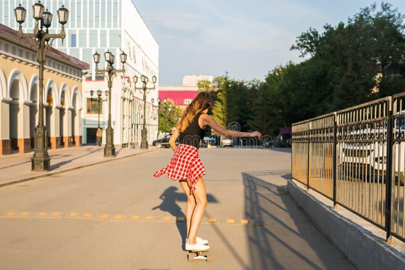 Летние отпуска, весьма спорт и концепция людей - счастливая девушка ехать современный скейтборд на улице города стоковая фотография rf