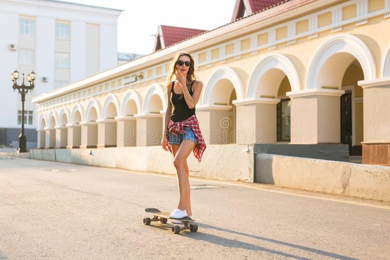 Летние отпуска, весьма спорт и концепция людей - счастливая девушка ехать современный скейтборд на улице города стоковое фото