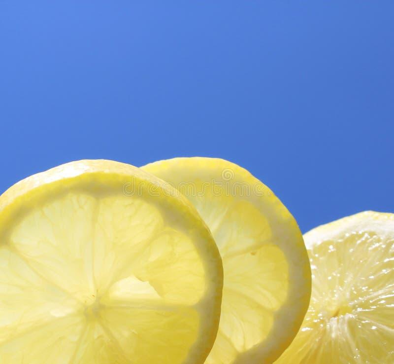 Летние отпуска 3 куска лимона перед солнцем и голубым небом стоковые изображения