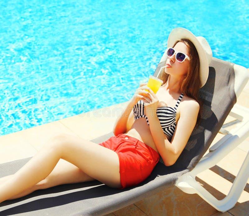 Летние отпуска - милая молодая женщина выпивает сок от чашки стоковое изображение