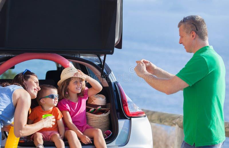 Летний отпуск семьи сидя в автомобиле стоковое фото rf