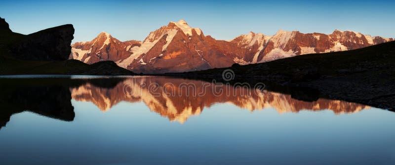 Лето в швейцарских Альп, зона Murren, обозревая Eiger, горы Monch и Jungfrau отразили в озере Grauseewli, стоковое фото