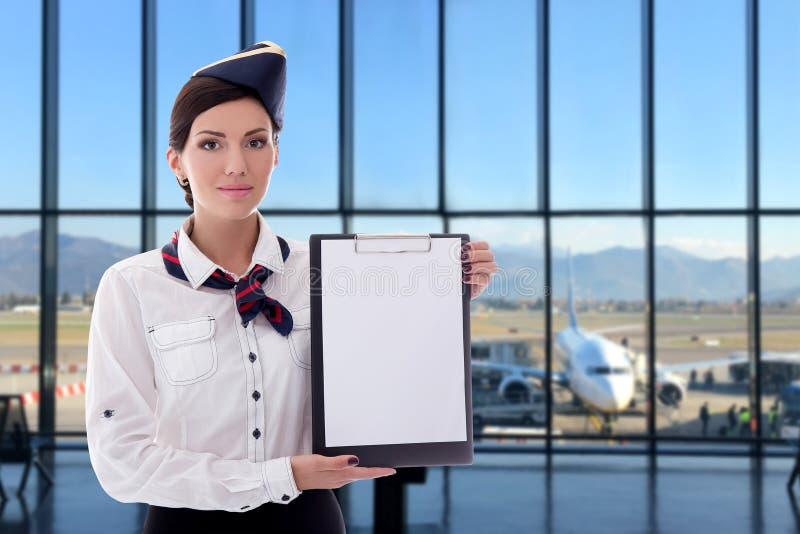 Лето, каникулы и концепция перемещения - stewardess держа пустую доску сзажимом для бумаги в аэропорте стоковое фото rf
