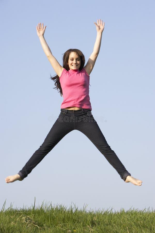 лето лужка девушки скача подростковое стоковая фотография rf