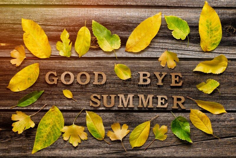 Лето на деревянной предпосылке, рамка до свидания надписи желтых листьев стоковые изображения