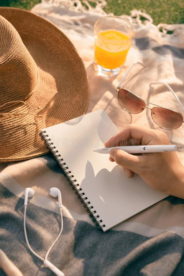 Лето - руки с сочинительством ручки на тетради в парке стоковая фотография