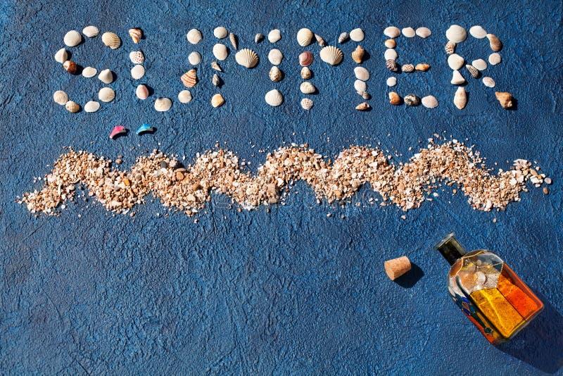 Лето слова сделало seashells, волны моря, песка золота, скача дельфинов, покрашенной стеклянной бутылки с пробочкой на голубом вз стоковые фото