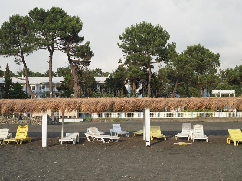Лето, солнце, дезертированный пляж побережья с шезлонгами Пляж морем с пустыми шезлонгами установил в ряд стоковое изображение rf