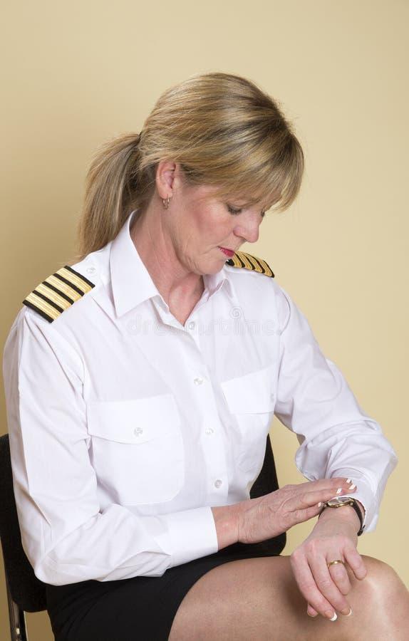 Летчик авиалинии проверяя ее вахту стоковая фотография rf