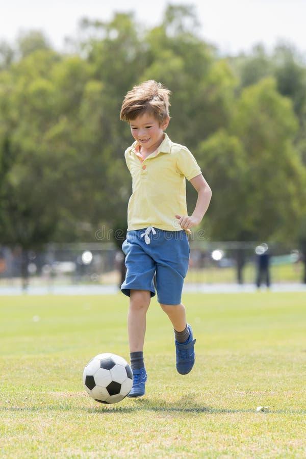 Леты футбола футбола маленького ребенка 7 или 8 старого наслаждаясь счастливого играя на поле парка города травы бежать и пиная ш стоковые изображения