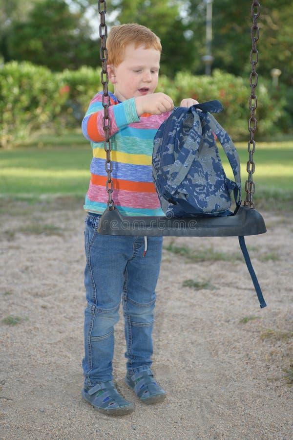 5 лет старого redheaded счастливого мальчика регулируя его рюкзак на качании перед идти обучить стоковая фотография rf
