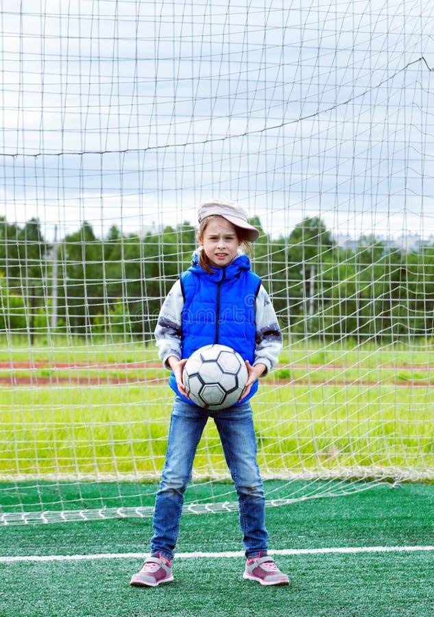 10 лет старой девушки стоят в стробе футбола как голкипер и держат шарик стоковые фото