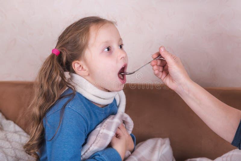 Лечение ребенка Больная девушка с шарфом лежит на кровати стоковые изображения