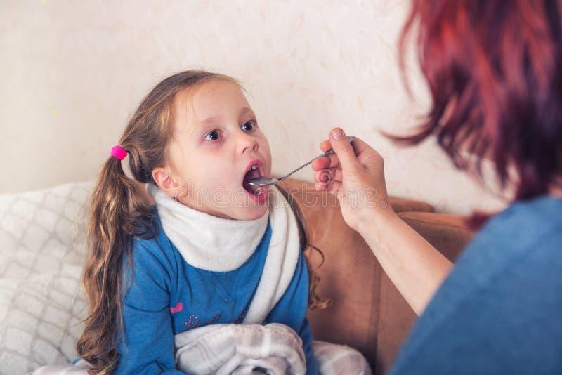 Лечение ребенка Больная девушка с шарфом лежит на кровати стоковая фотография rf