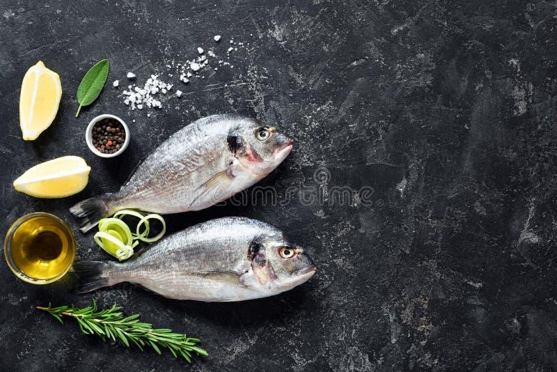 Лещ моря свежих рыб, травы, специи, оливковое масло и ингридиенты варить на каменной предпосылке шифера стоковое фото