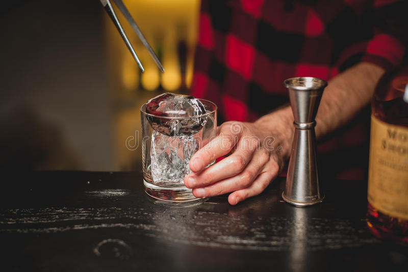 Лед бармена лить в стекле Бармен подготавливая питье коктеиля стоковые фотографии rf