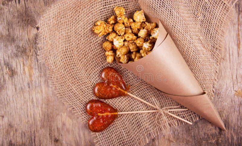 Леденец на палочке 2 в форме сердца и бумажная сумка попкорна карамельки на деревянной предпосылке стоковые фотографии rf