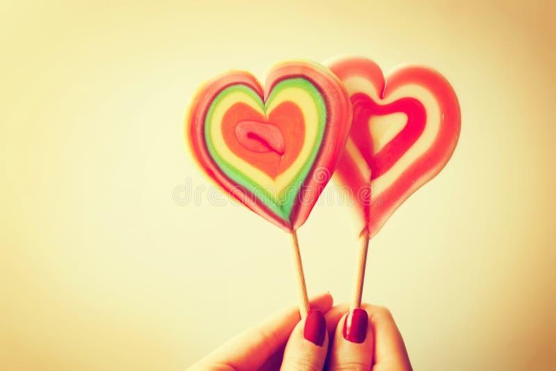 Леденцы на палочке красочного сердца форменные в руке женщины стоковое изображение