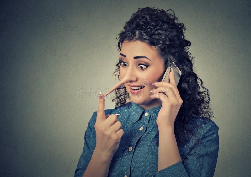 Лжец работы с клиентом с длинным носом Женщина говоря на мобильном телефоне говоря лож стоковые фотографии rf