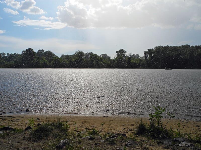 Ливень с солнцем над рекой Остатки на летний день рекой стоковое фото rf