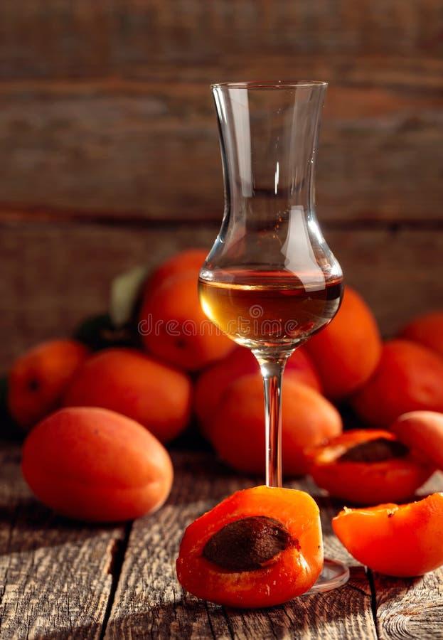 Ликер абрикоса и свежие абрикосы на старом деревянном столе стоковые фотографии rf