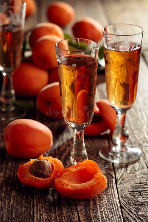 Ликер абрикоса и свежие абрикосы на старом деревянном столе стоковое фото