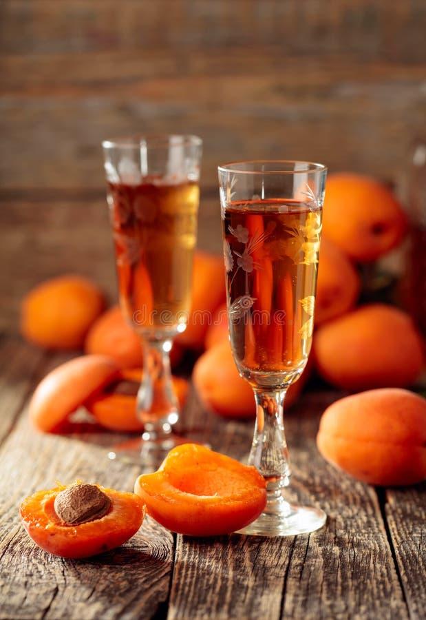 Ликер абрикоса и свежие абрикосы на старом деревянном столе стоковое изображение rf