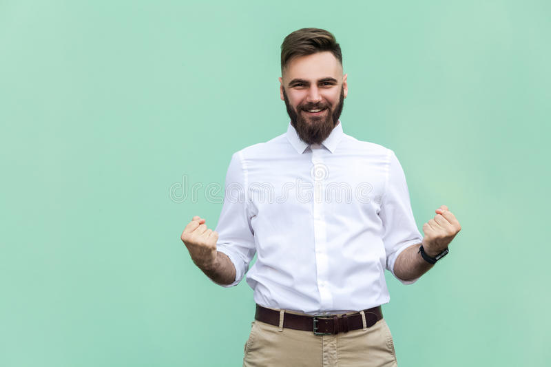 Ликование бизнесмена для его успеха Изолированный на салатовой предпосылке стоковая фотография