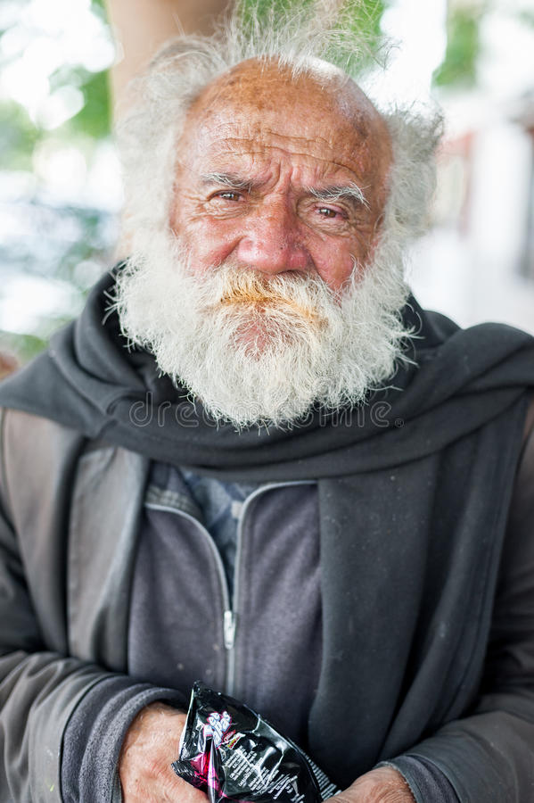 ЛИМА, ПЕРУ - 15-ОЕ АПРЕЛЯ 2013: Неизвестный бездомный человек с серой бородой есть помадки в Лиме, Перу стоковые фото