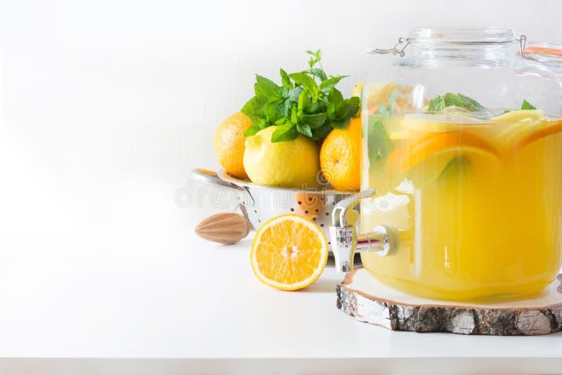 Лимонад лета здоровый в большом опарнике каменщика с лимоном, апельсином и мятой на белой таблице скопируйте космос конец вверх стоковое фото