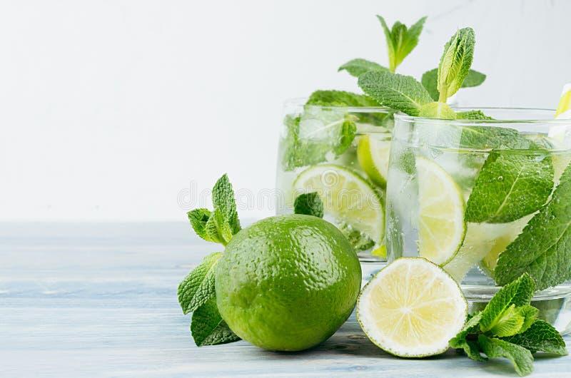 Лимонад лета холодный в 2 влажных стеклах с мятой, известкой, льдом, соломой на винтажной белой предпосылке гипсолита, космосе эк стоковая фотография