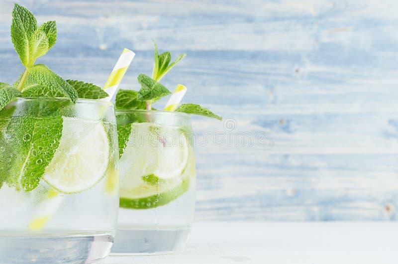 Лимонад лета холодный в 2 влажных стеклах с мятой, известкой, льдом, соломой на винтажной голубой деревянной доске, космосе экзем стоковые изображения