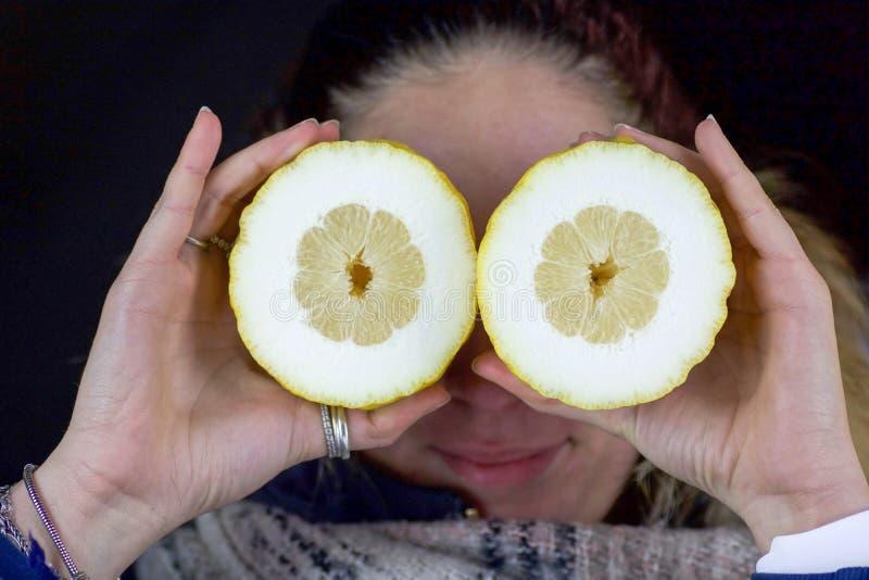 Лимоны владением 2 рук девушки половинные как наблюдает стоковое фото rf