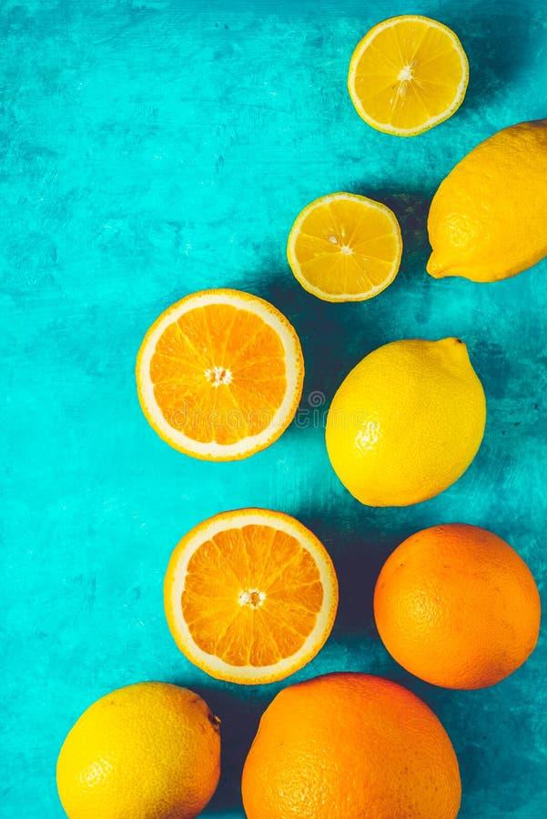 Лимоны и апельсины на cyan вертикали предпосылки стоковая фотография rf
