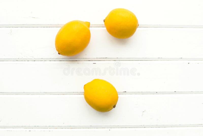 Лимоны на белой деревянной предпосылке стоковые изображения rf
