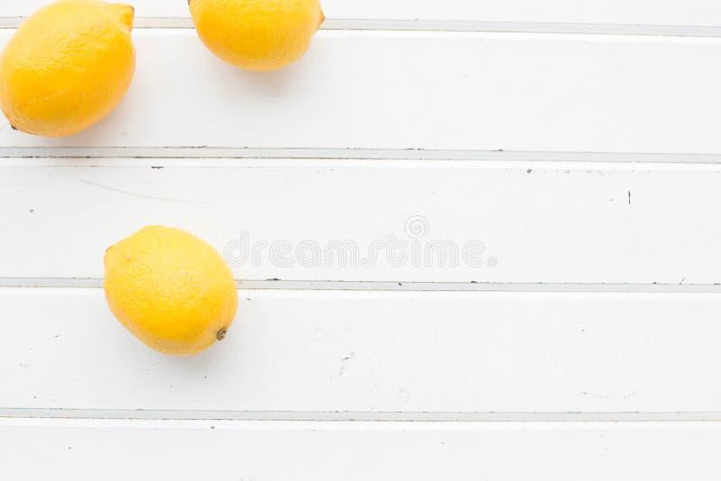 Лимоны на белой деревянной предпосылке стоковое фото