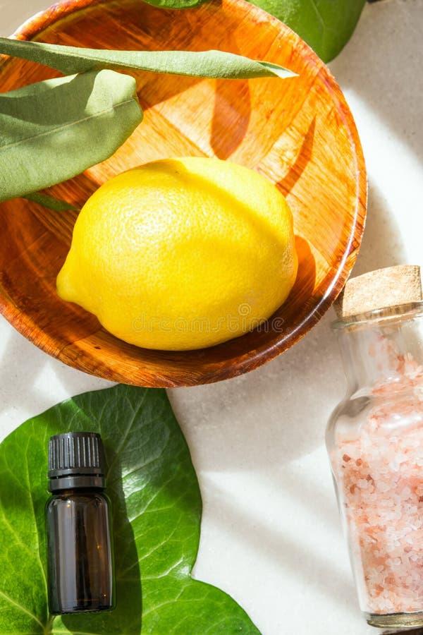 Лимон взгляд сверху зрелый желтый в деревянной бутылке эфирного масла шара на зеленом плюще выходит розовое гималайское соль на б стоковые фото