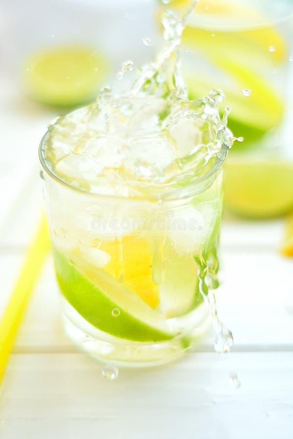 Лимон и известка коктеиля в стекле с водой брызгают стоковое изображение